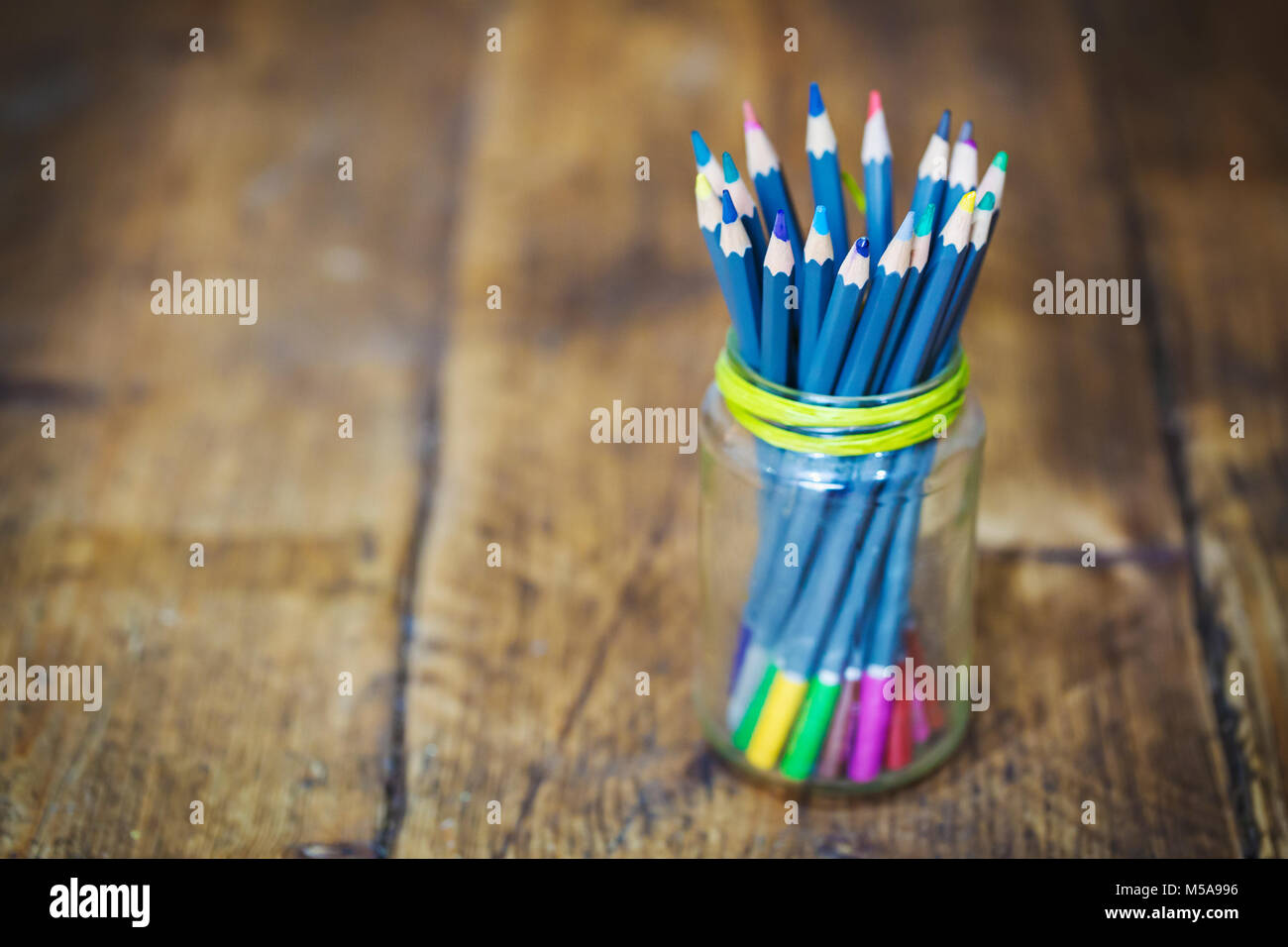Close up of a glsas jar with blue colouring pencils on wooden table. - Stock Image