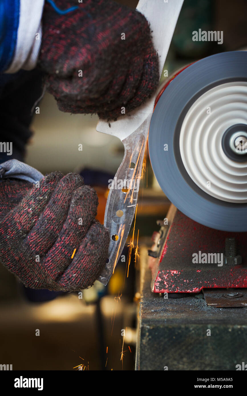 Close up of man in workshop holding a newly cut knife blade, smoothing the surface with a rotating surface grinder. - Stock Image