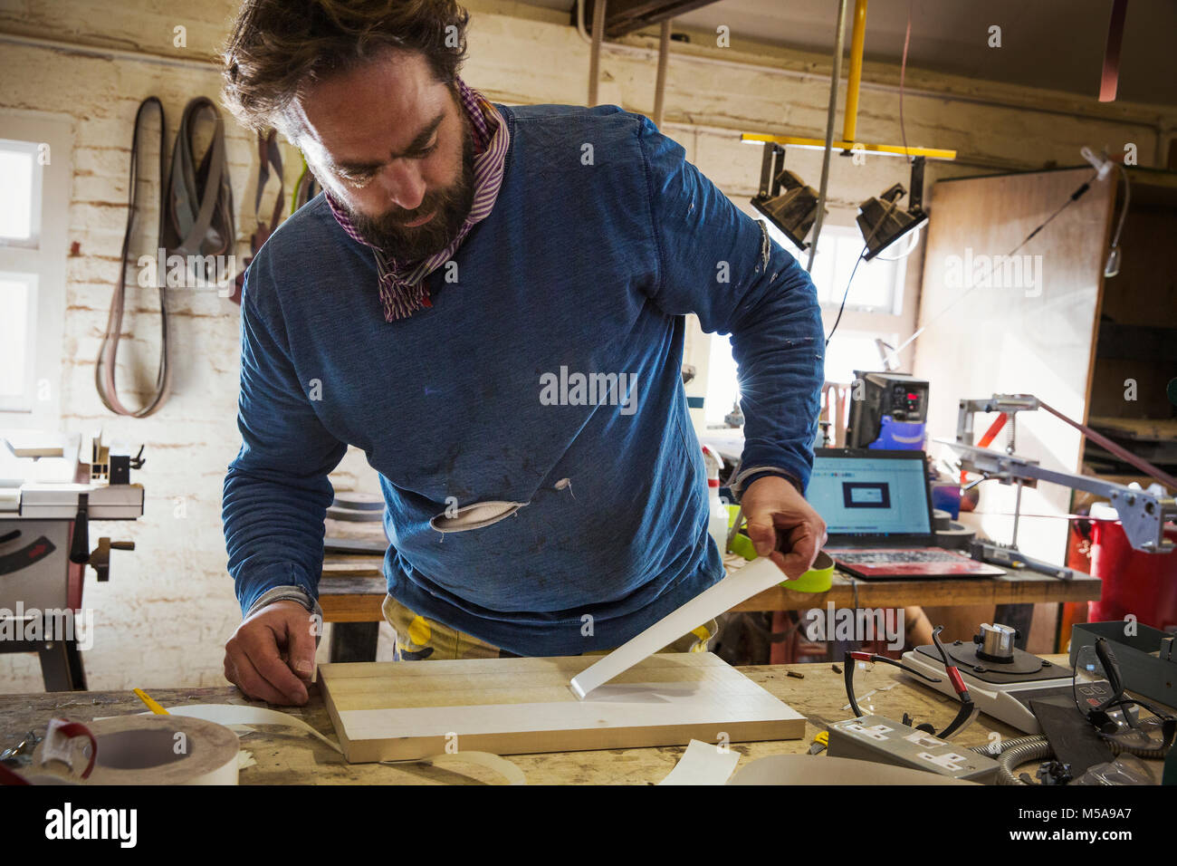 A craftsman in a workshop at a bench, stripping a protective layer off a flat wooden board. - Stock Image