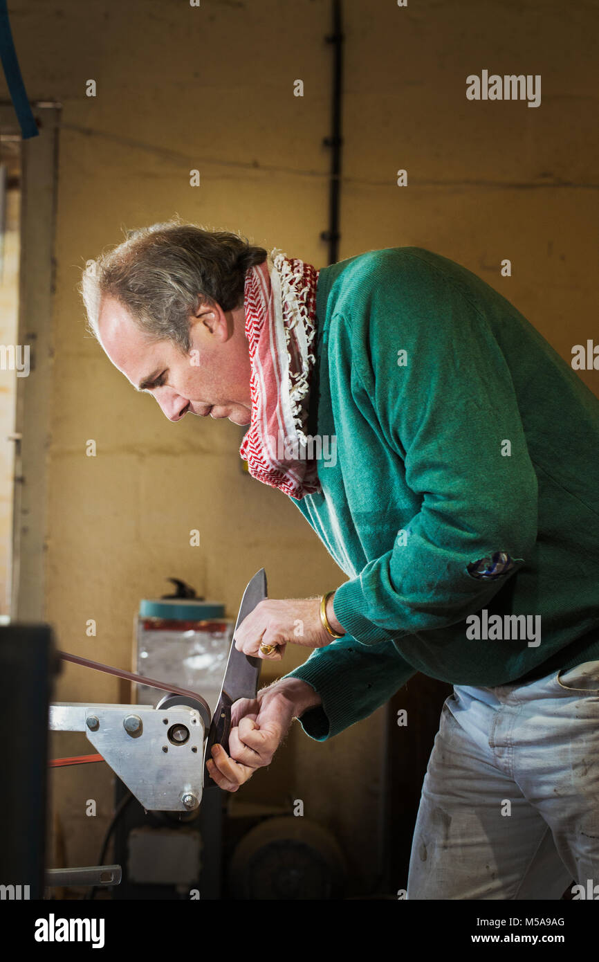 A craftsman in a knife makers workshop, holding a kitchen knife and shaping and finishing the wooden handle with - Stock Image