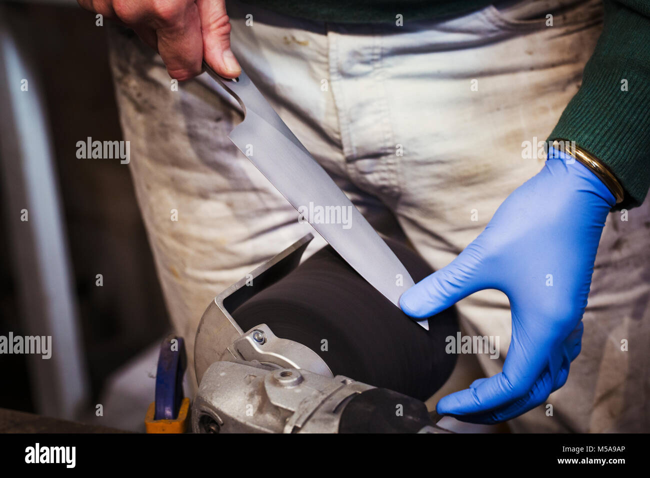 Close up of a craftsman's hand in a blue glove, sharpening and honing the tip of a knife blade on a sanding - Stock Image