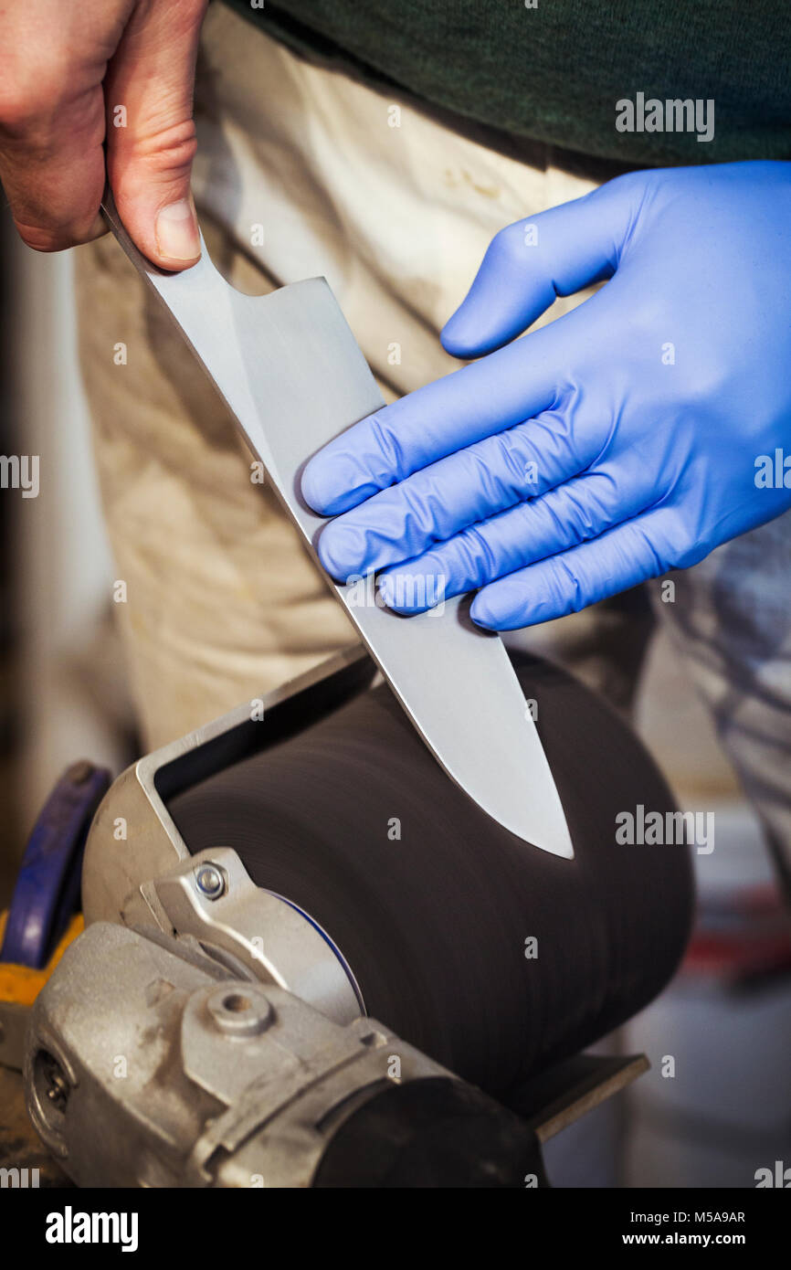 Close up of a craftsman in a workshop, sharpening and honing the blade of a kitchen knife using a rotary sanding - Stock Image