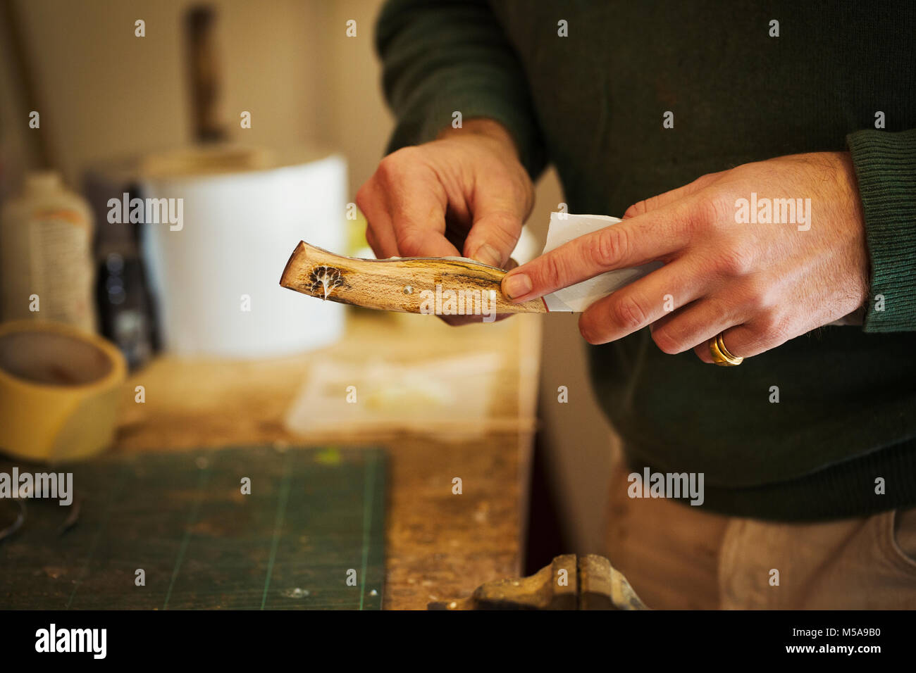 Close up of a craftsman fixing a smooth shaped wooden handle onto a newly made knife blade. - Stock Image