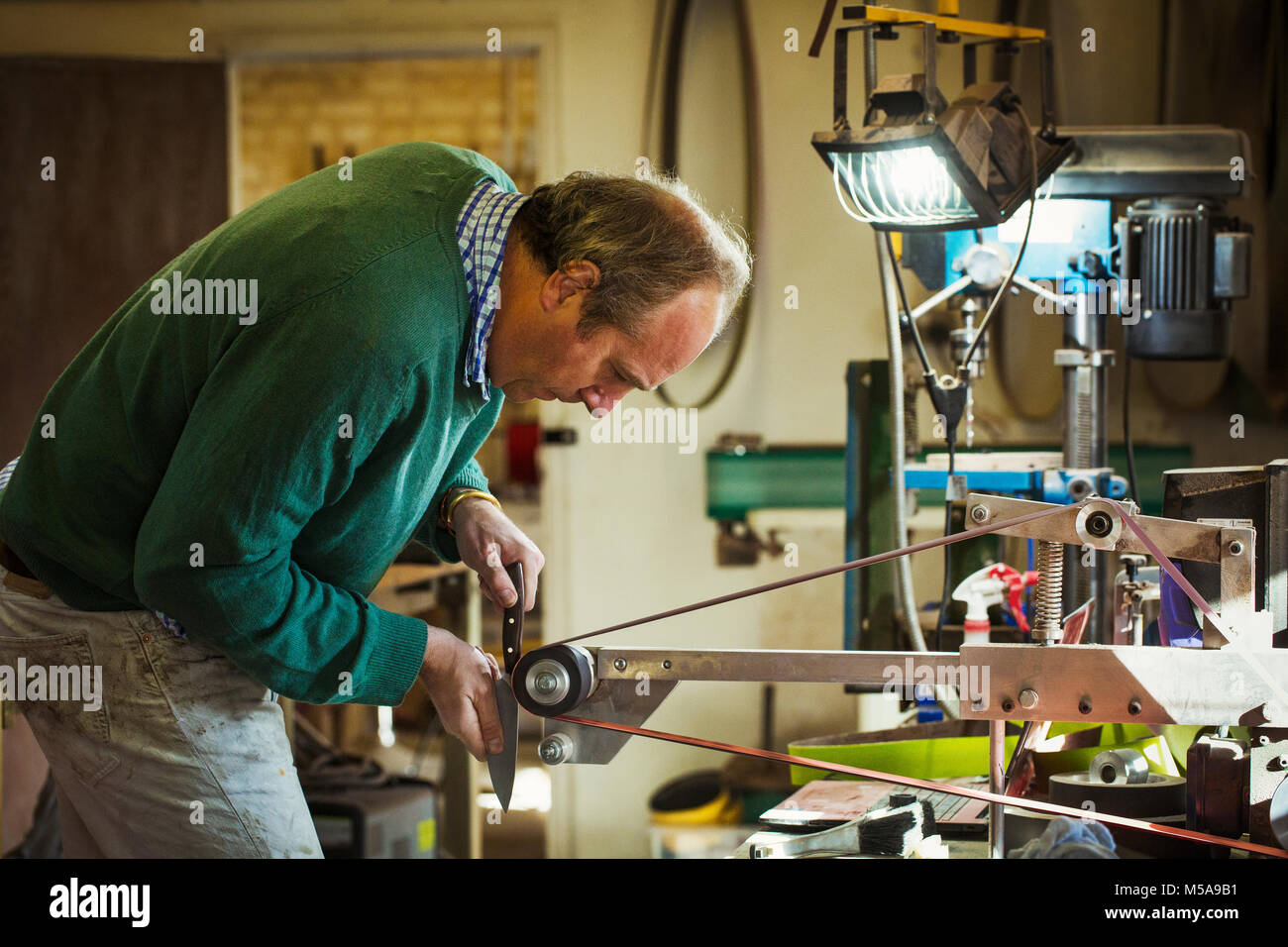 A craftsman in a workshop, holding a knife and smoothing and finishing a handle with a sanding wheel. - Stock Image