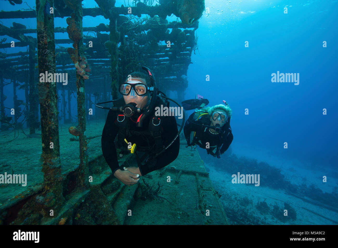 Two divers swimming along the remaining structure of a shipwreck. - Stock Image