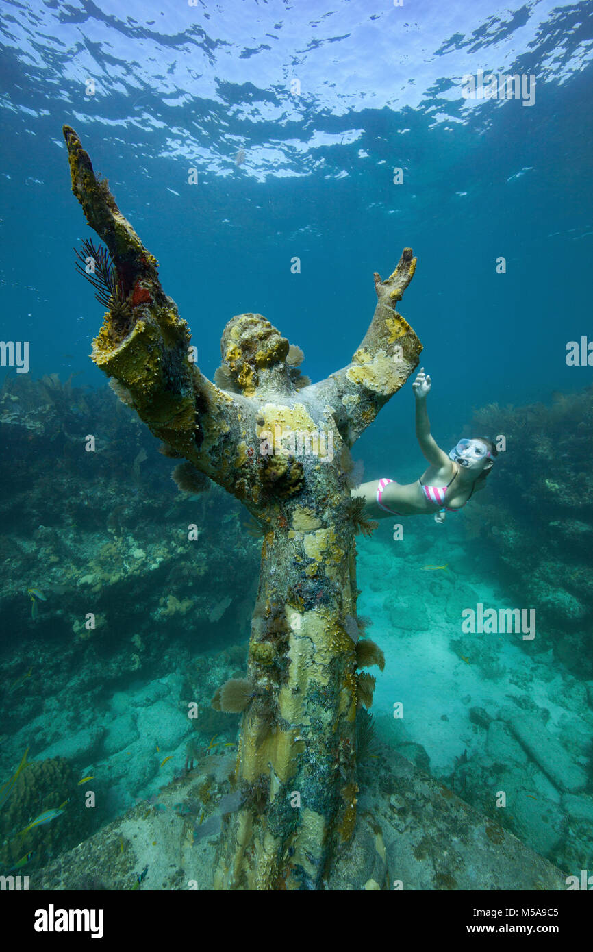 A young woman snorkels near the Christ of the Abyss Statue, Key Largo, Florida Keys.  The bronze statue was submerged - Stock Image