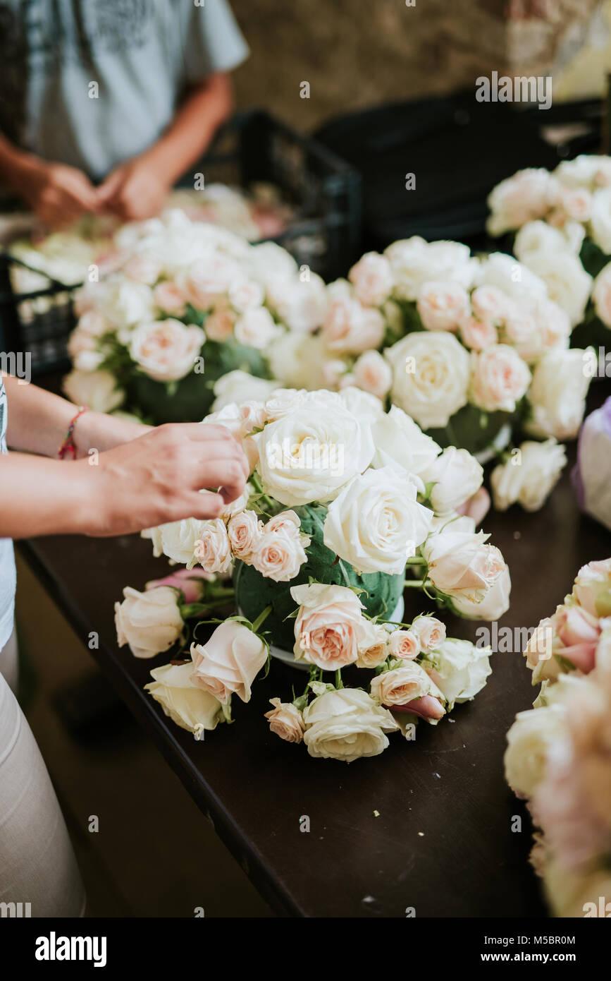 Florist arranging flowers for wedding - Stock Image