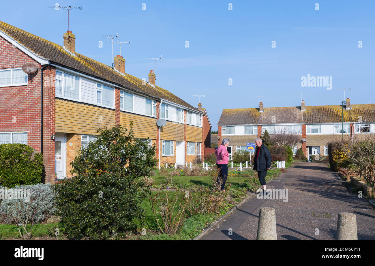 pair-of-neighbours-standing-outside-talking-in-a-close-in-england-M5CY11.jpg