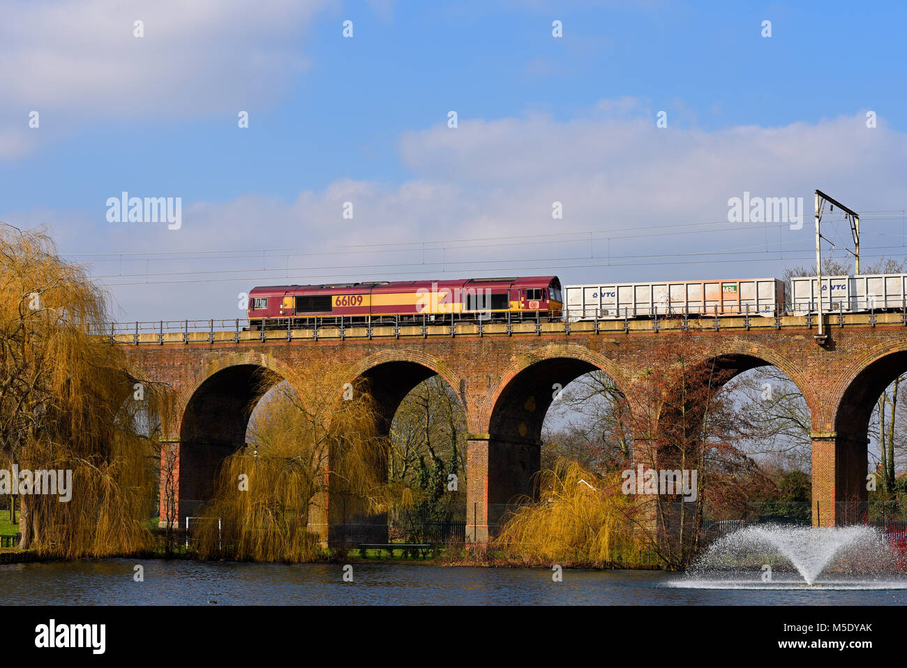 DBS Class 66 diesel electric hauling a freight train crossing railway viaduct in Central Park, Chelmsford, Essex, Stock Photo