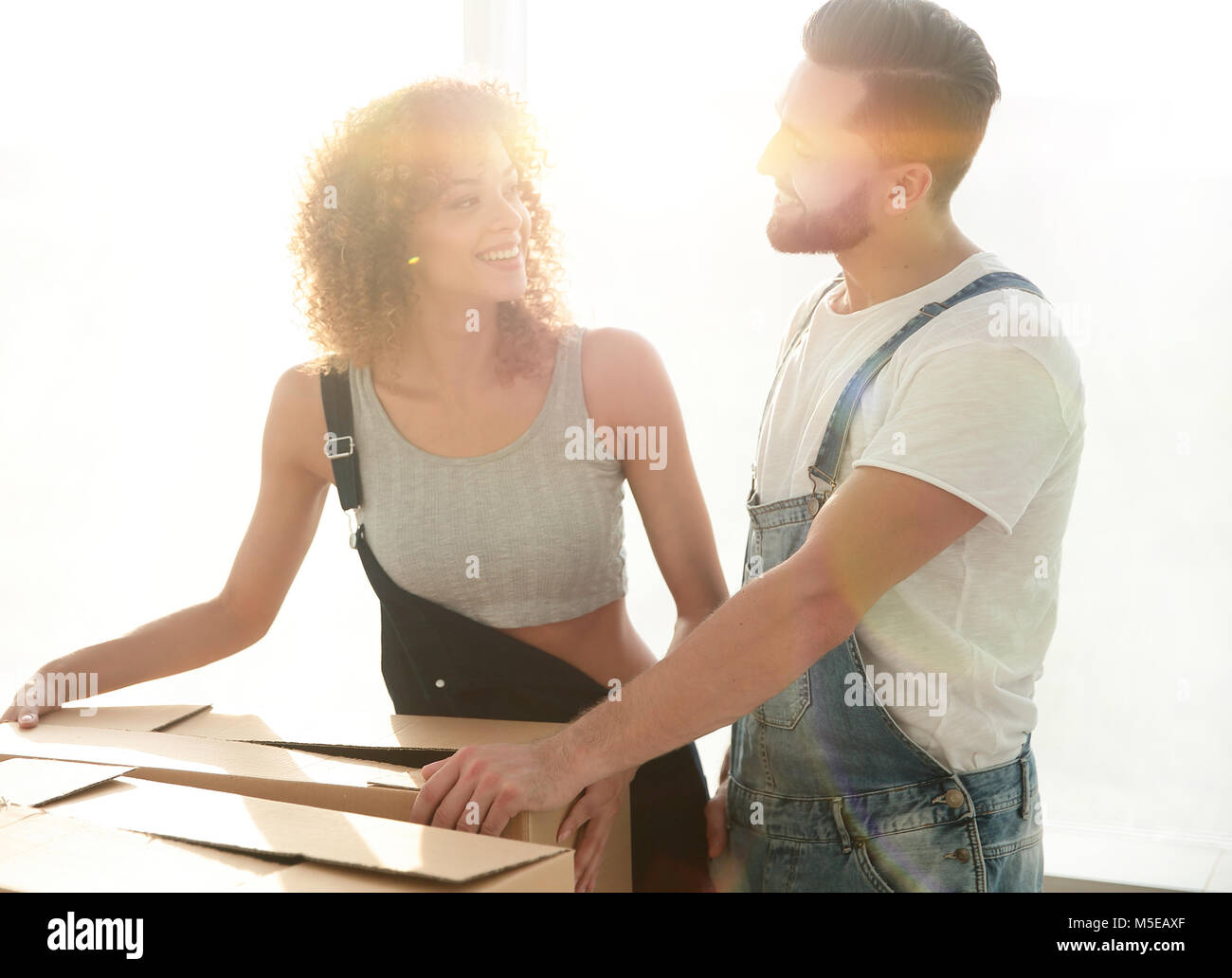 Newlyweds unpack boxes in a new apartment. - Stock Image