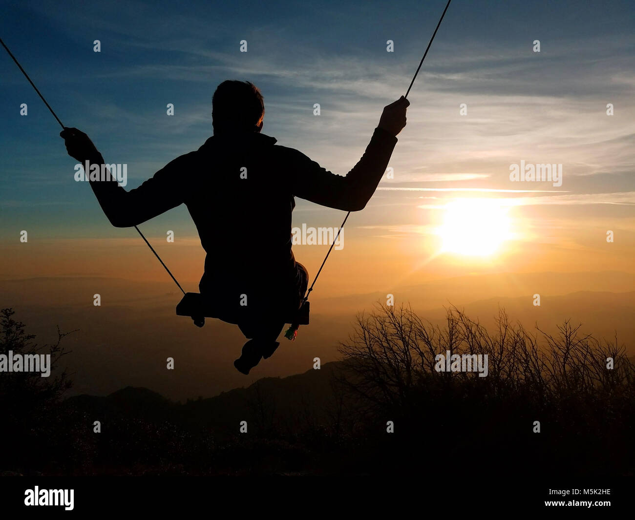 A silhouette of a person swinging towards the sun on the top of Mt. Lowe, Los Angeles, San Gabriel National Forest - Stock Image