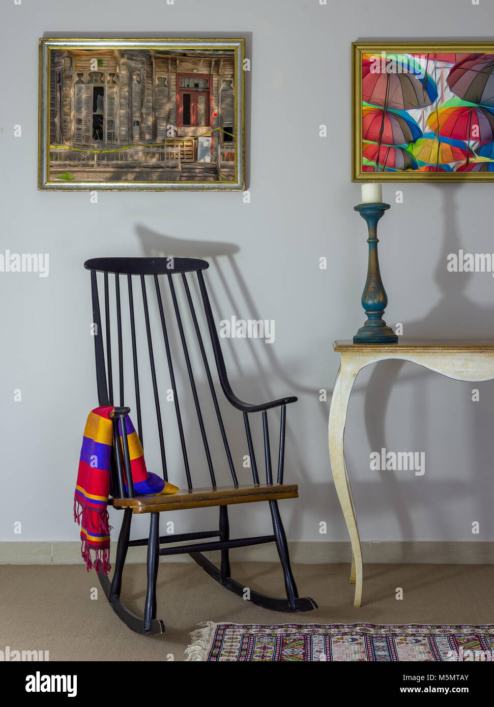 Interior shot of vintage rocking chair, old style table, candlestick on background of off white wall with two hanged - Stock Image