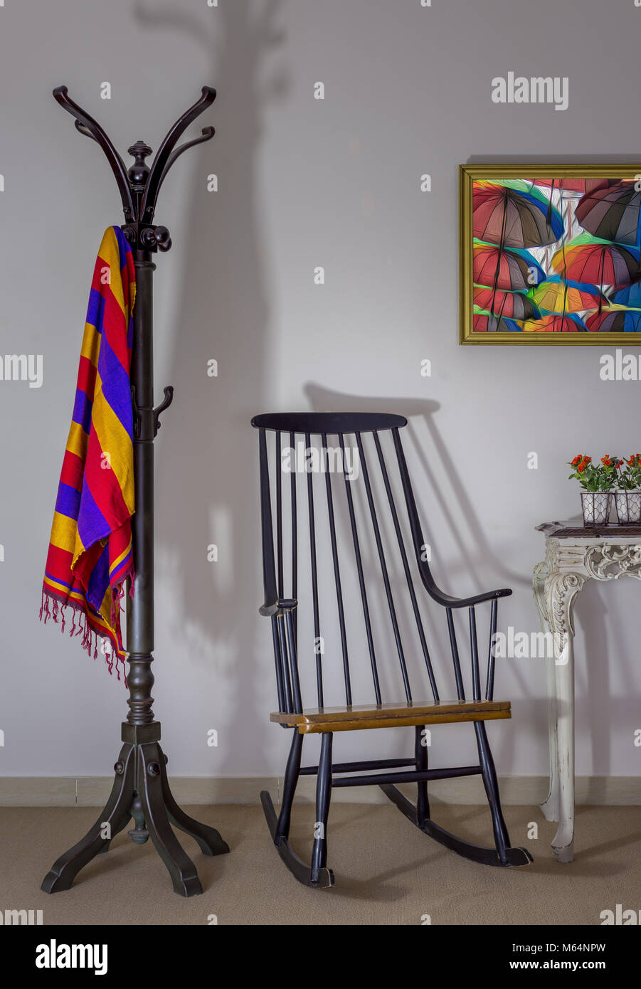 Interior shot of vintage rocking chair, coat hanger and flower pot on old style vintage table on background of off - Stock Image