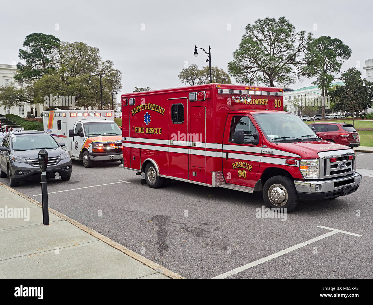 Fire Rescue paramedic ambulance with a Haynes Ambulance parked behind responding to a medical emergency in Montgomery - Stock Image