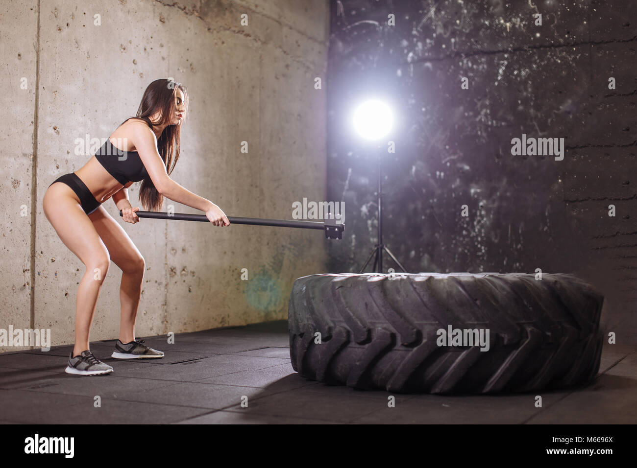 woman smashing large tire with sledgehammer during intense workout in fit gym - Stock Image
