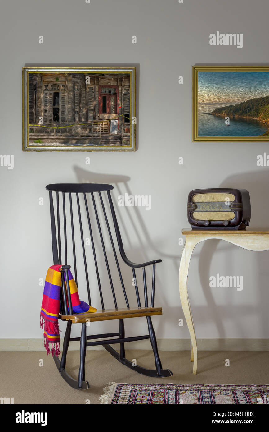 Interior shot of vintage rocking chair and old radio on old style vintage table on background of off white wall - Stock Image