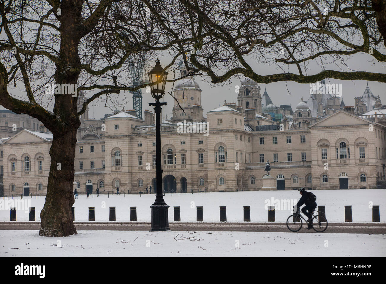 A cyclist cycles in the snow past Horesguard's Parade - Stock Image