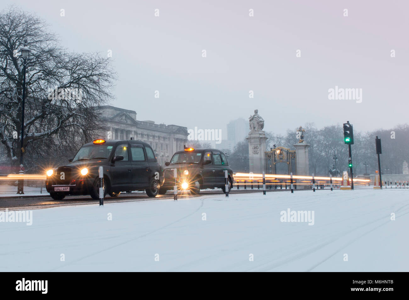 Taxis and traffic outside Buckingham Palace in the snow - Stock Image