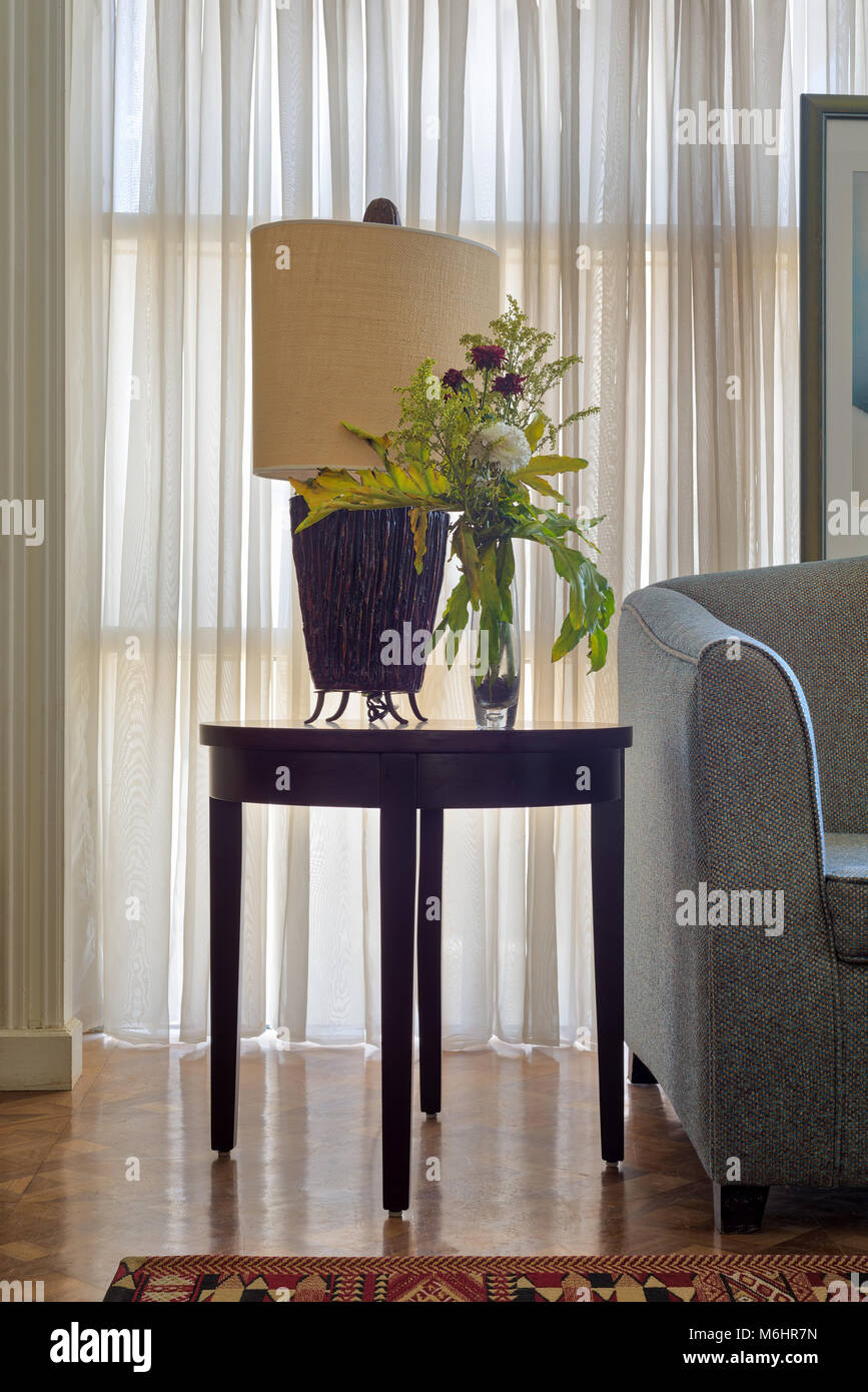 Interior shot of  table lamp and colorful flowers planter on small dark brown wooden table on background of big - Stock Image
