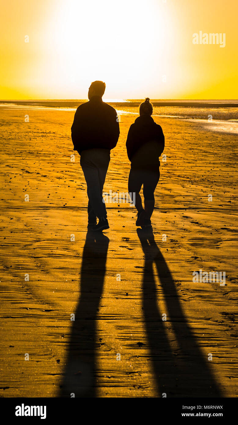 couple-of-people-walking-on-a-sandy-beach-in-the-morning-towards-the-M6RNWX.jpg