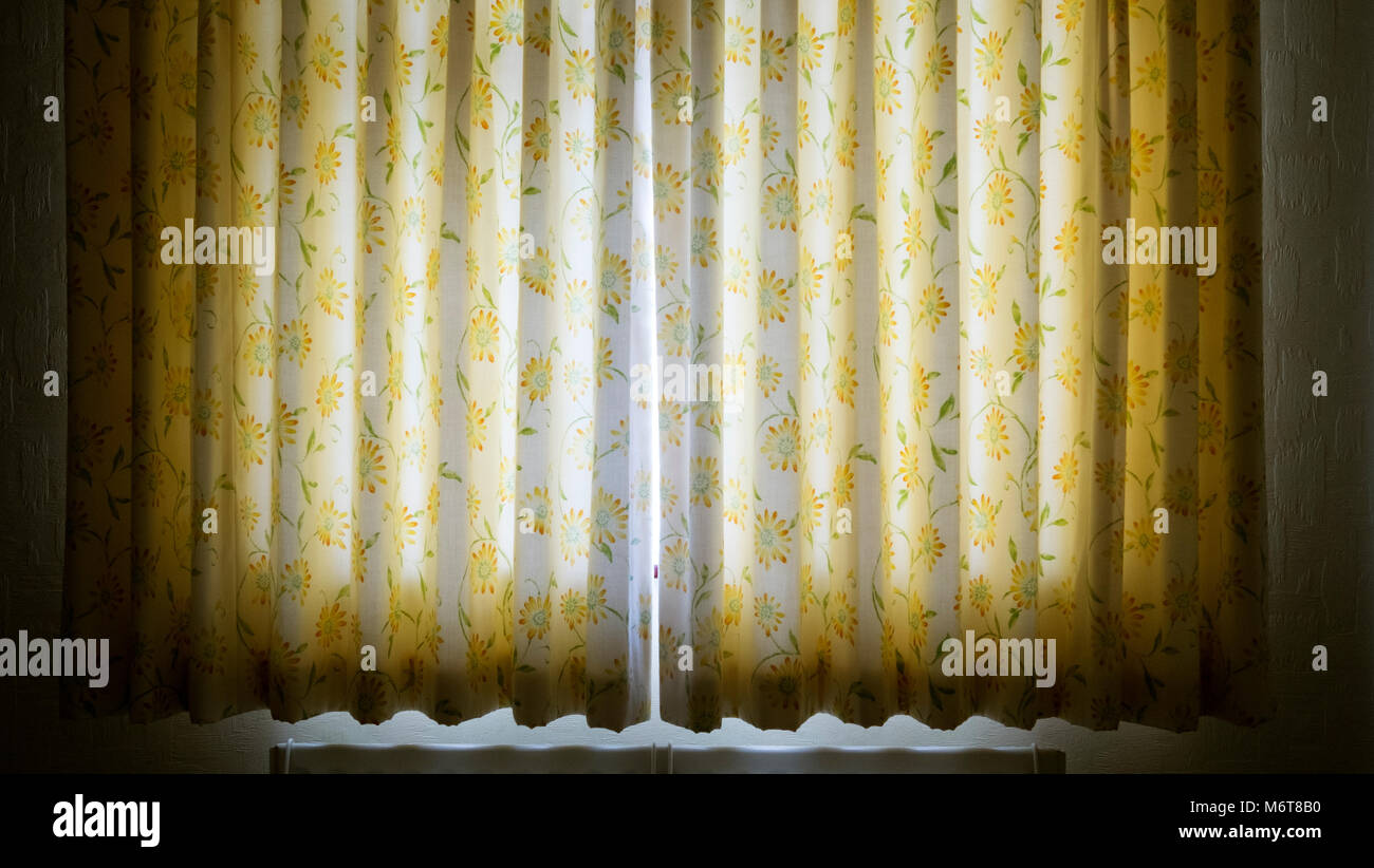 Early morning sunlight streaming through a crack in a pair of closed double panel curtains. - Stock Image