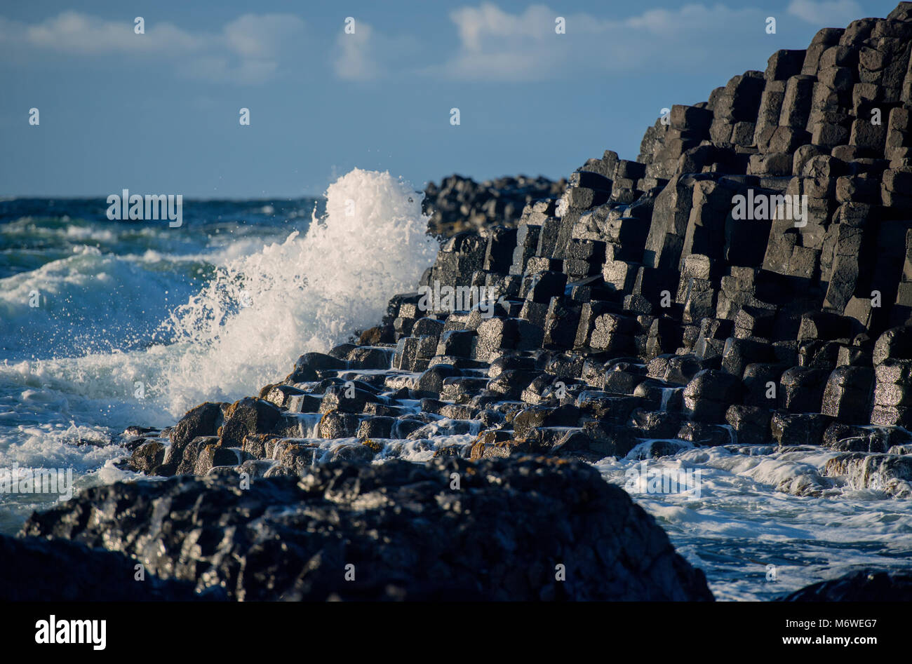 Wave hitting the Giant's Causeway in County Antrim, Northern Ireland - Stock Image