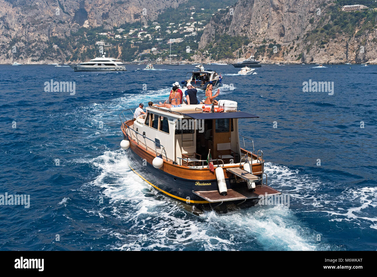 tourists on a boat trip around the island capri, bay of naples, italy. - Stock Image