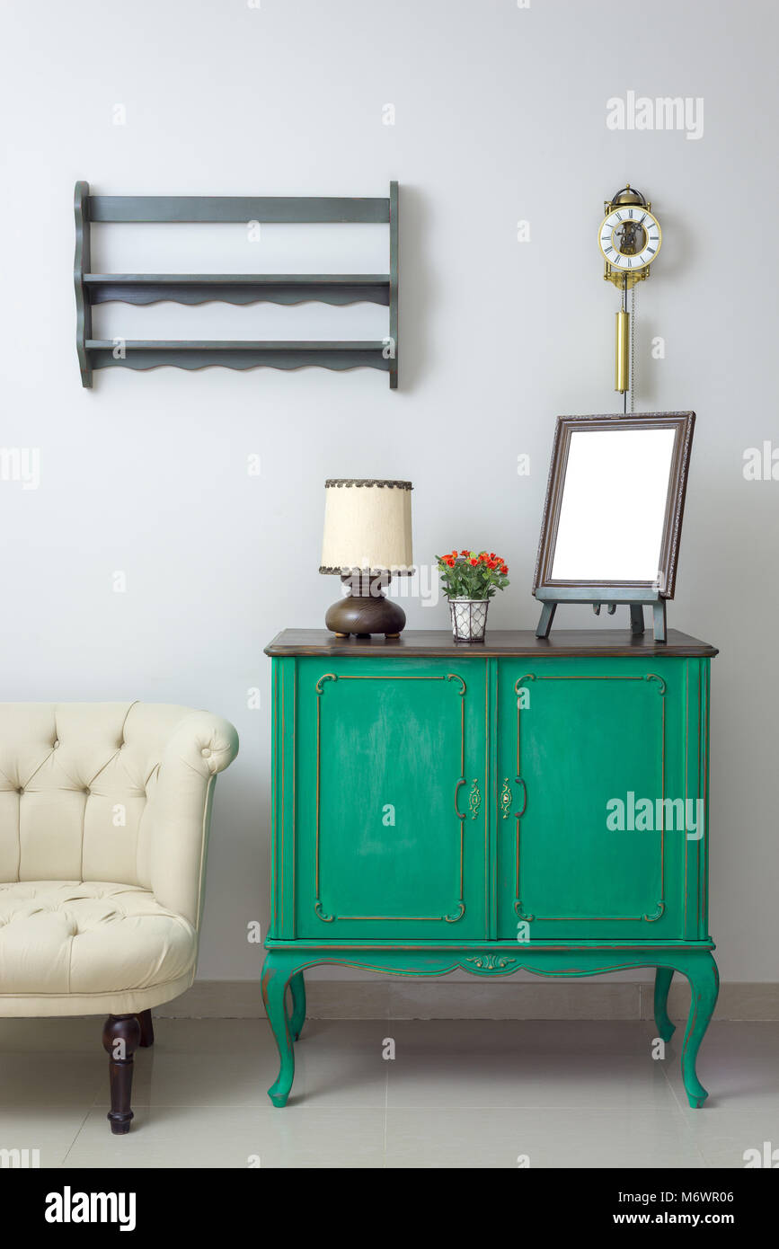 Wooden green vintage sideboard with empty wooden ornate brown desktop photo frame, flower planter, table lamp and - Stock Image