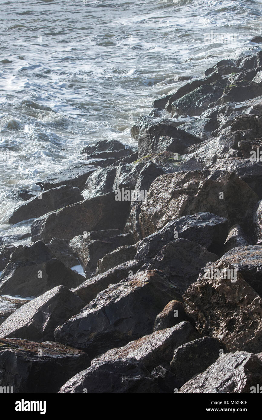 a rocky seashore on the seafront with rocks and waves crashing onto the shore during a stormy weather day. rough - Stock Image