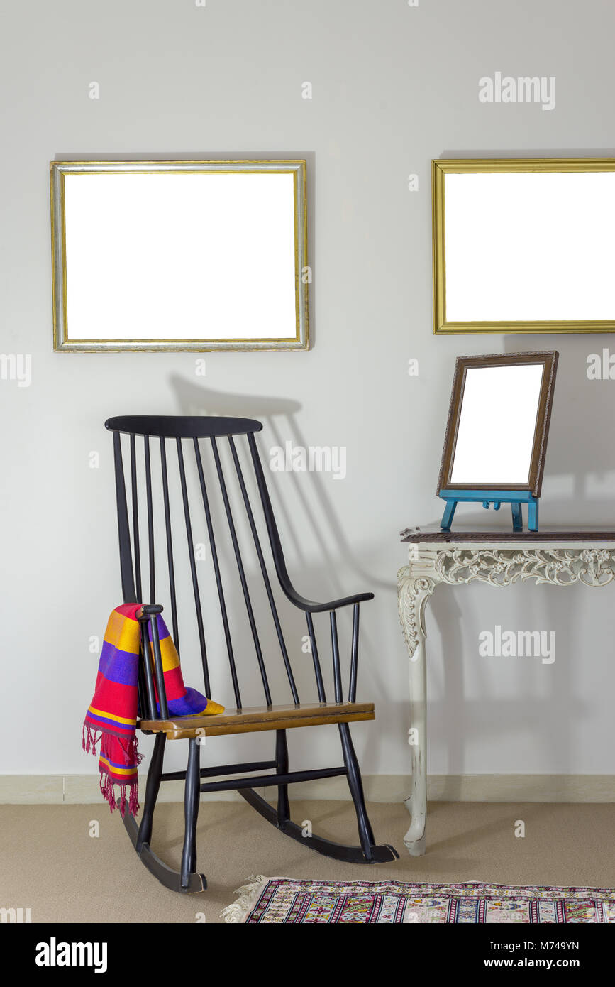 Interior shot of classic rocking chair and wooden ornate brown desktop photo frame on old style vintage table on - Stock Image