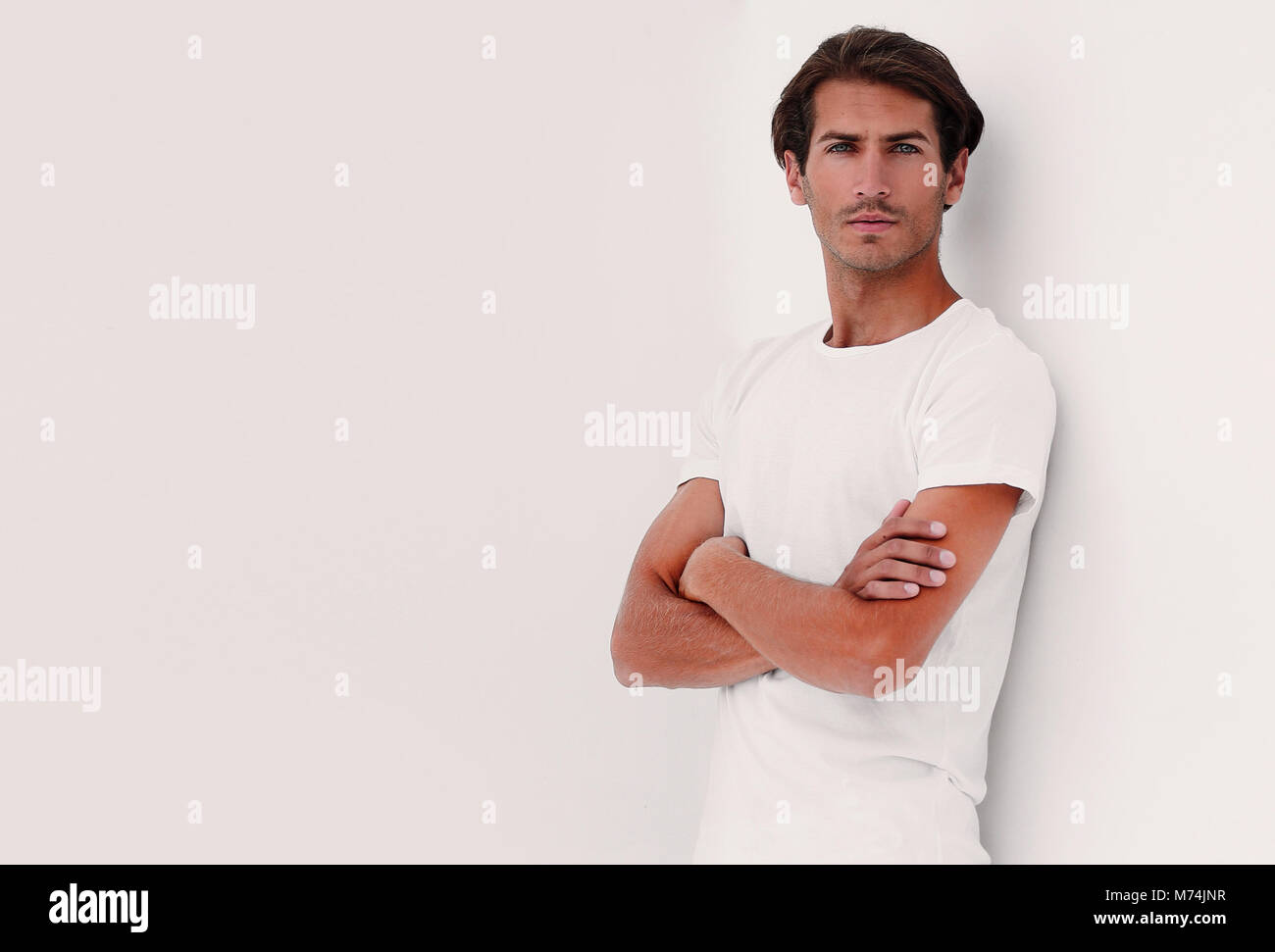 background image of a pensive man leaning on wall - Stock Image