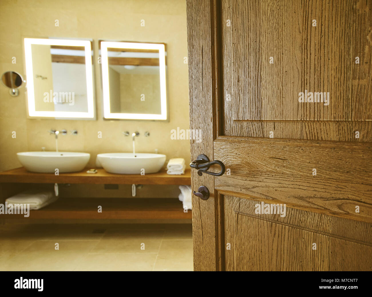 bathroom for an open wooden door. Two sinks for bathrooms and two mirrors. Tap water flowing - Stock Image