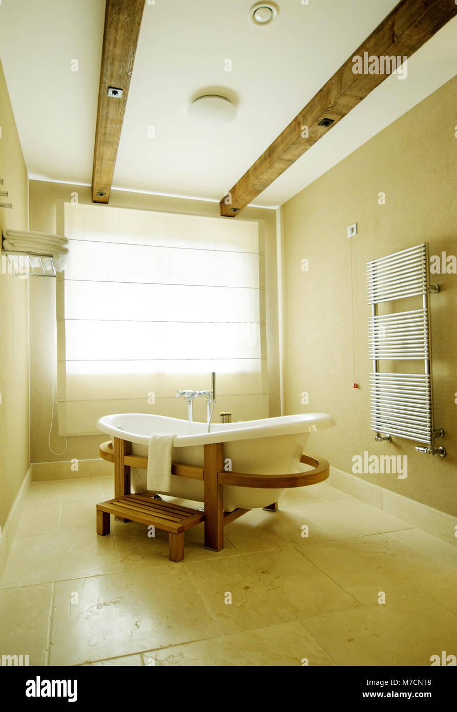 beautiful white tub against the window. bath stands on a wooden stand - Stock Image