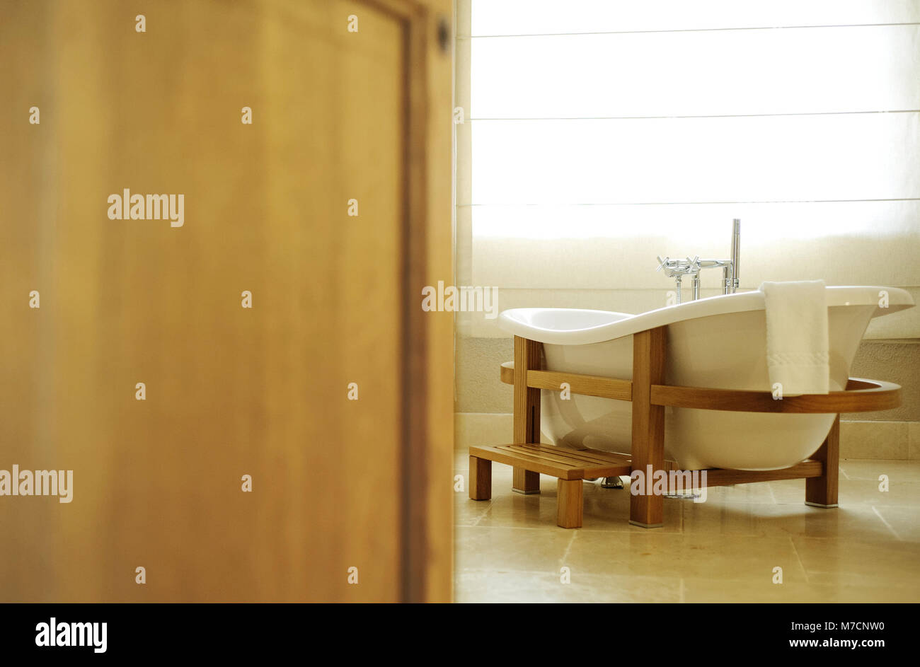 beautiful white bath for an open door. Bath stands in a wooden frame - Stock Image