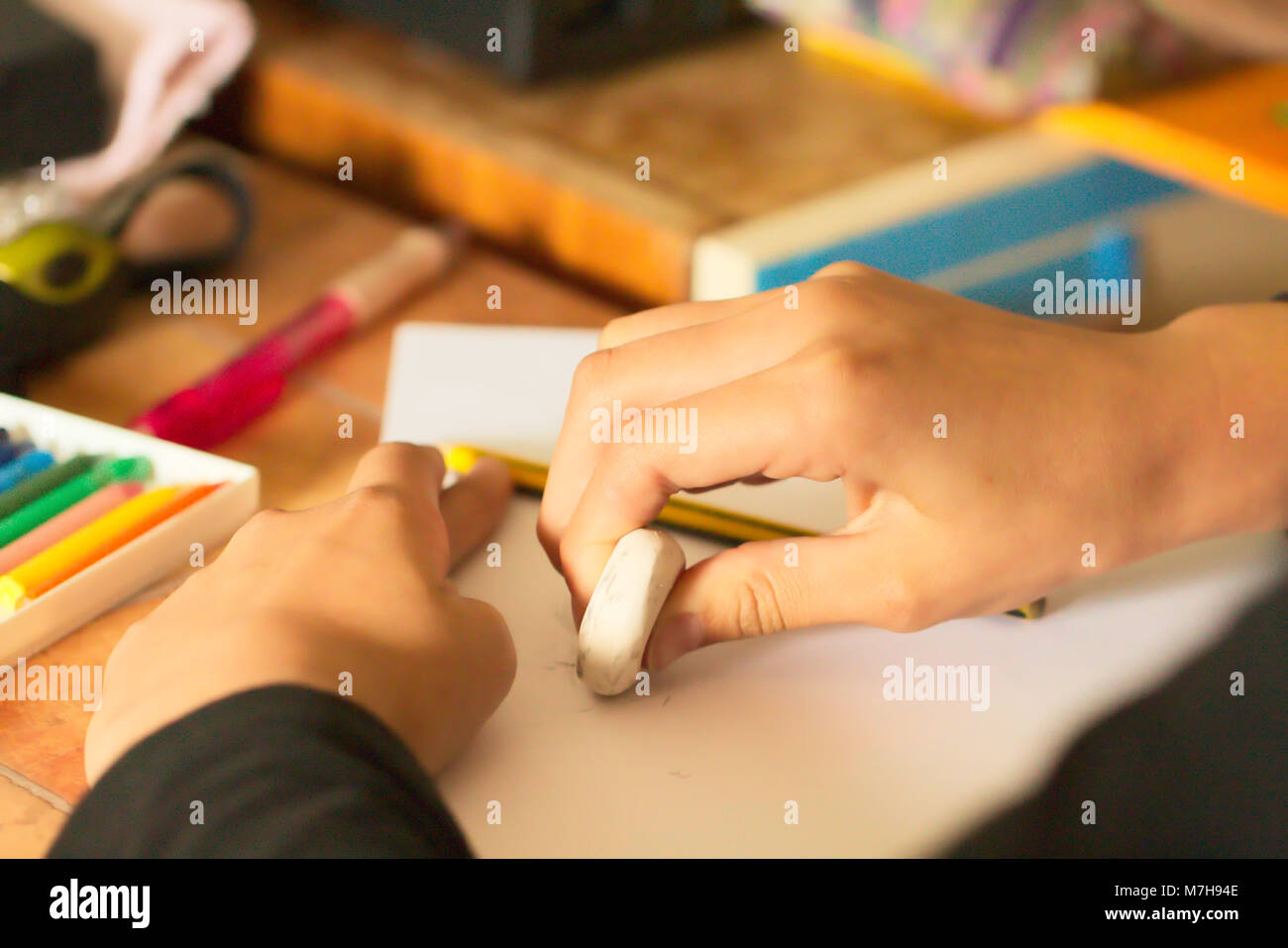 Teenager´s Hand Holding Rubber and Editing a Drawing - Stock Image