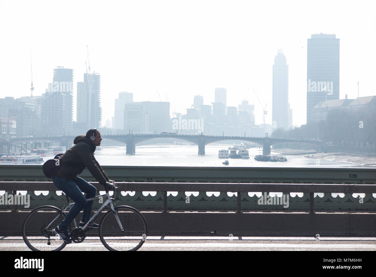 A cyclist crosses the River Thames on a cold and misty morning - Stock Image