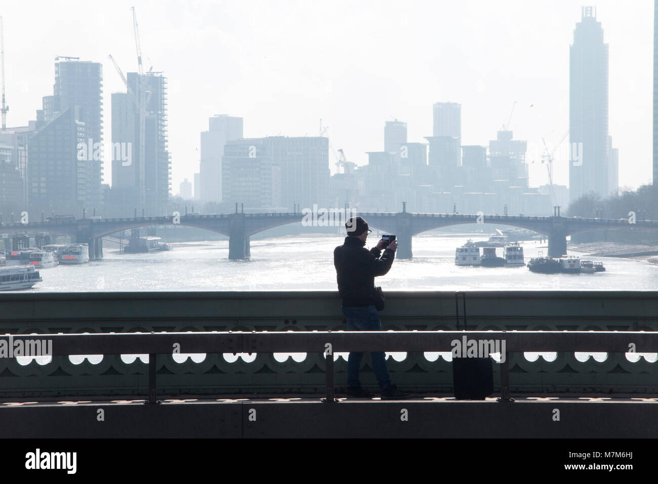 A man takes a photograph of the River Thames on a cold and misty morning - Stock Image