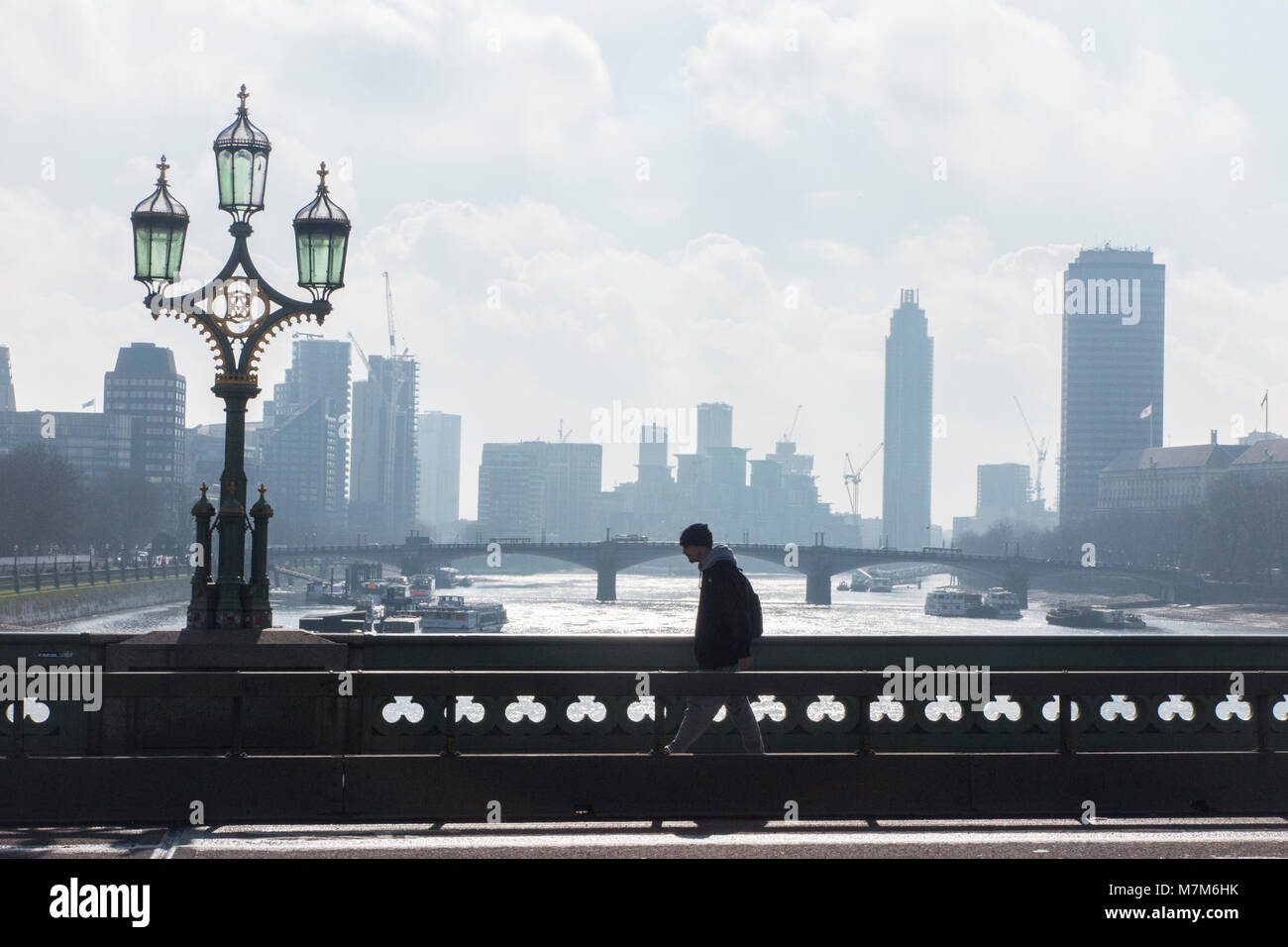 A pedestrian crosses the River Thames on a cold and misty morning - Stock Image