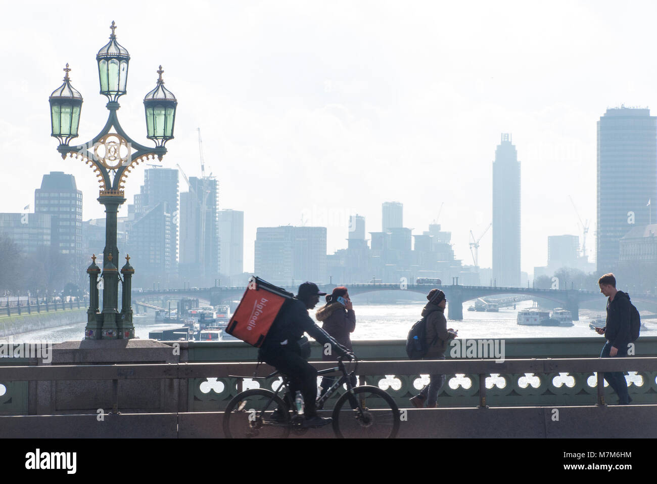 A food delivery rider crossed the River Thames on a cold and misty morning - Stock Image