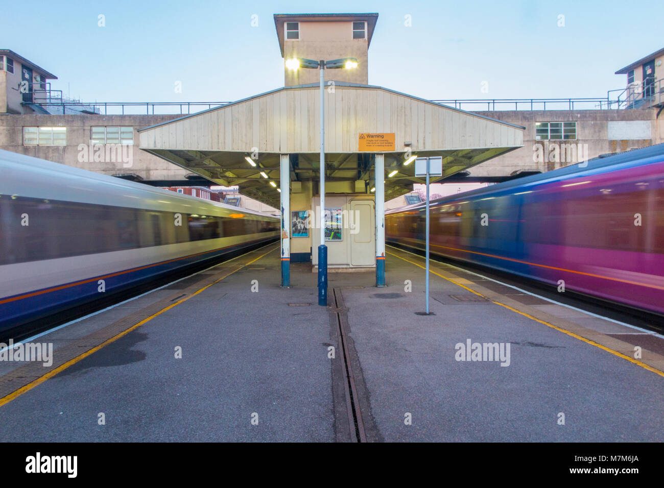 Woking station in Surrey with trains storming past the platforms on their way to and from London - Stock Image