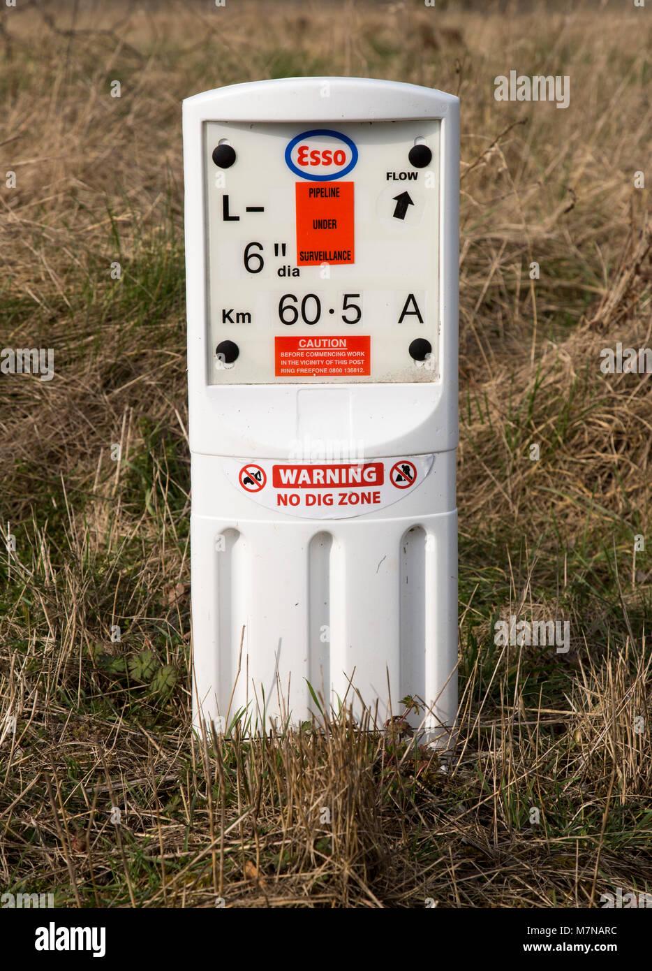 Close up of Esso gas pipeline under surveillance marker warning no dig zone, Salisbury Plain, Wiltshire, England, - Stock Image