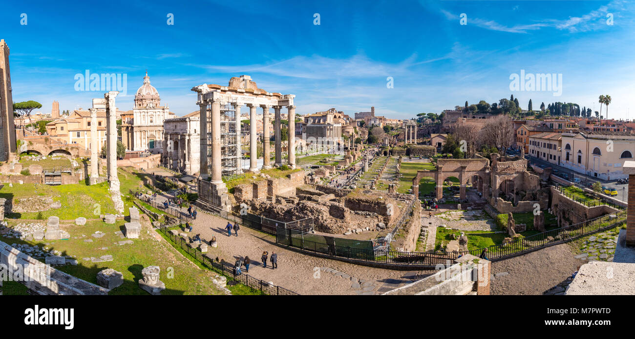 The ruins of the Roman Forum in Rome, Italy with the Colosseum visible in the back - Stock Image
