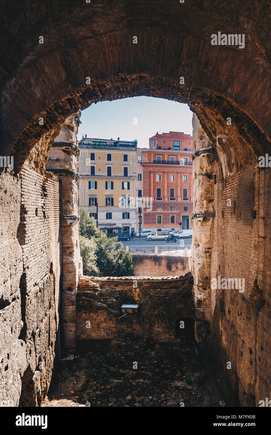 Archway in Colosseum with Rome city streets visible - Stock Image