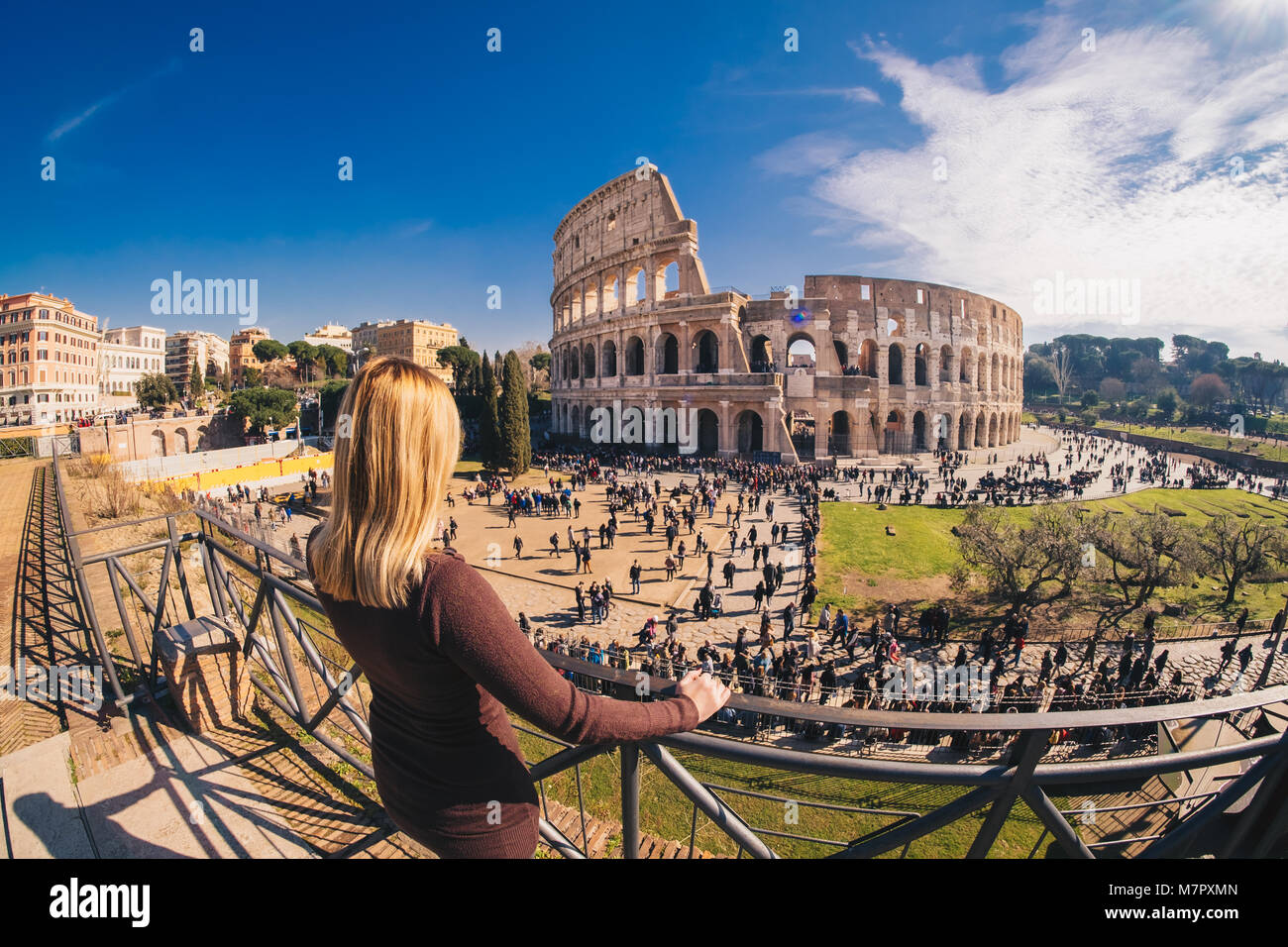 Woman tourist enjoying the view of the Roman Colosseum in Rome, Italy - Stock Image