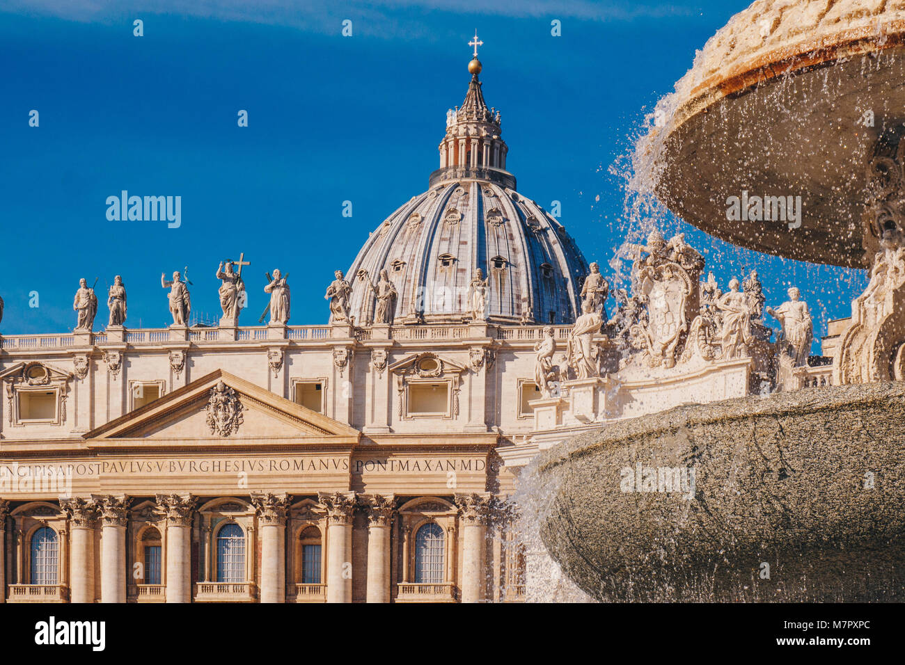 Saint Peter's Basilica  dome and the fountain in front in Vatican City, Rome, Italy. Focus on the dome. - Stock Image