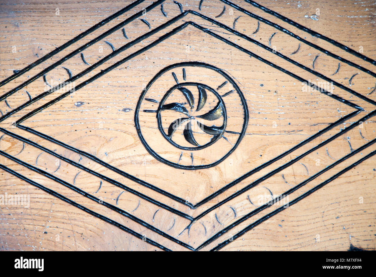 Old carved decorations in wooden fireplace surround of village pub Tilshead, Wiltshire, England, Uk - Stock Image
