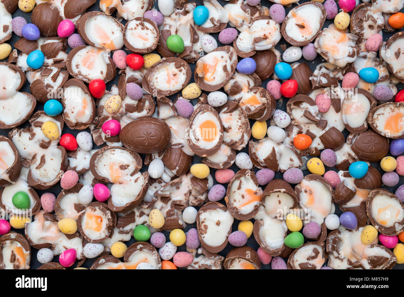 Have a smashing Easter.  Smashed Cadburys creme eggs with chocolate mini eggs on a slate background - Stock Image
