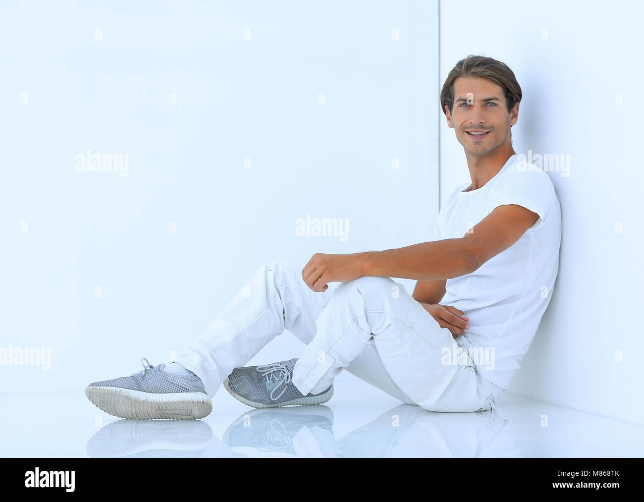 pensive boy sitting near the wall - Stock Image