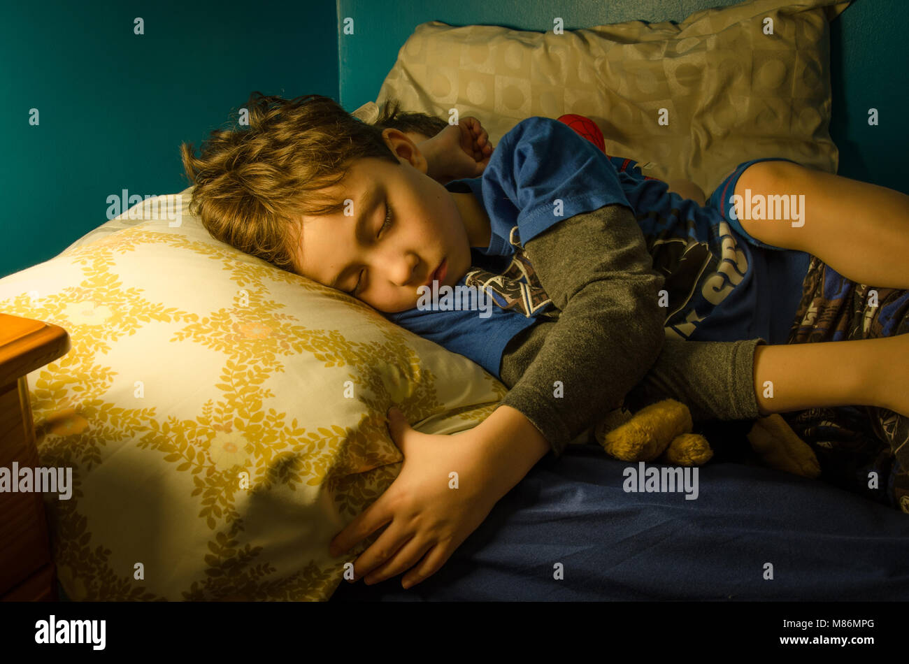 two-young-brothers-asleep-in-the-same-bed-at-nighttime-the-scene-is-M86MPG.jpg