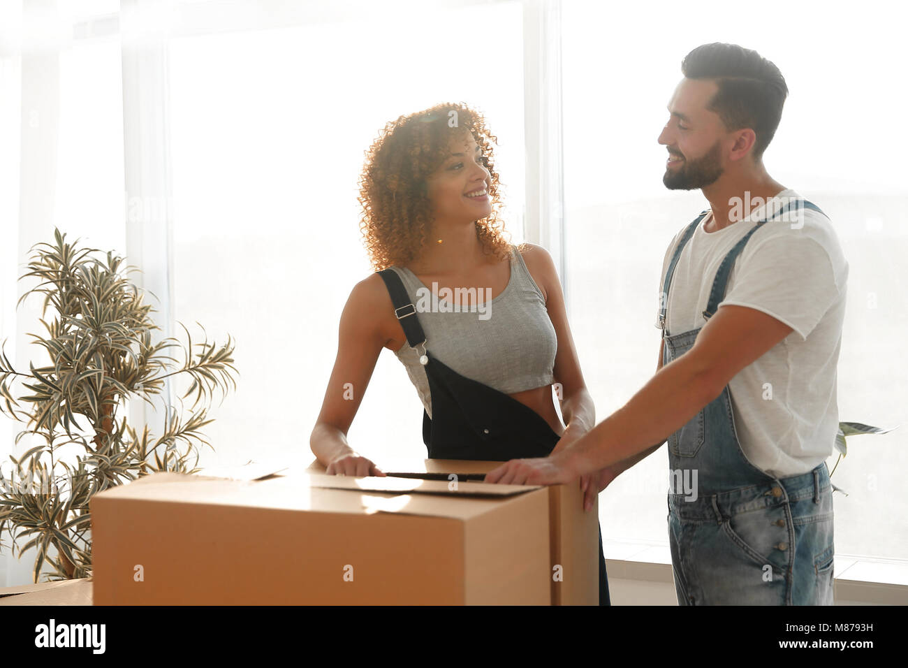 Newlyweds carry boxes in a new apartment. - Stock Image